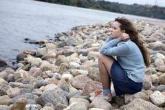 Mujer joven que se sienta en la playa Imagen de archivo libre de regalías