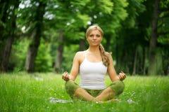 Mujer joven que se sienta en la posición de la yoga en el parque Imagen de archivo