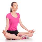 Mujer joven que se sienta en la posición de loto Imagen de archivo