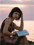Mujer joven que se sienta en la puesta del sol Fotografía de archivo