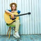 Mujer joven que se sienta en la silla que sostiene la guitarra acústica Fotografía de archivo