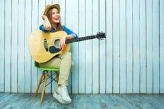 Mujer joven que se sienta en la silla que sostiene la guitarra acústica Foto de archivo libre de regalías