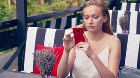 Mujer joven que se sienta en la tabla en el café que mira el teléfono que es infeliz con la desintegración 4k, cámara lenta, inte almacen de video