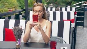 Mujer joven que se sienta en la tabla en el café que mira el teléfono que es infeliz con la desintegración 4k, cámara lenta, inte almacen de metraje de vídeo