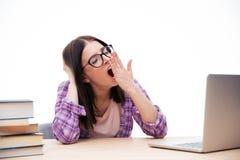 Mujer joven que se sienta en la tabla y que bosteza Imagen de archivo