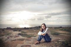 Mujer joven que se sienta en la tierra Fotos de archivo