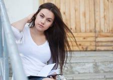 Mujer joven que se sienta en las escaleras Foto de archivo libre de regalías