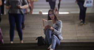 Mujer joven que se sienta en las escaleras en el subterráneo y que lee un libro metrajes