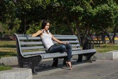 Mujer joven que se sienta en las escaleras y que escucha la música Fotos de archivo