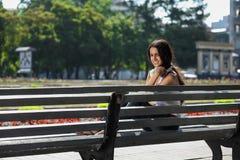 Mujer joven que se sienta en las escaleras y que escucha la música Foto de archivo
