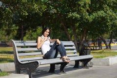 Mujer joven que se sienta en las escaleras y que escucha la música Fotografía de archivo