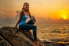 Mujer joven que se sienta en las rocas por el mar y que mira la salida del sol en una isla tropical Imagen de archivo