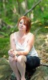 Mujer joven que se sienta en las sombras - maderas Foto de archivo libre de regalías