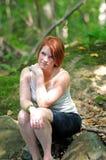Mujer joven que se sienta en las sombras - maderas Imagen de archivo