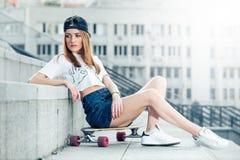 Mujer joven que se sienta en longboard en el paisaje urbano Fotografía de archivo