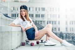 Mujer joven que se sienta en longboard en el paisaje urbano Foto de archivo libre de regalías