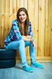 Mujer joven que se sienta en los neumáticos autos contra la pared de madera Fotos de archivo