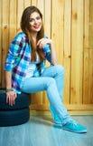 Mujer joven que se sienta en los neumáticos autos contra la pared de madera Foto de archivo libre de regalías
