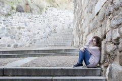 Mujer joven que se sienta en los pasos de progresión Fotografía de archivo libre de regalías