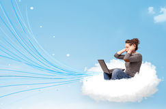 Mujer joven que se sienta en nube con el ordenador portátil Imágenes de archivo libres de regalías