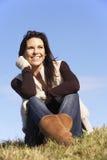 Mujer joven que se sienta en parque Fotos de archivo libres de regalías