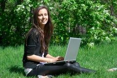 Mujer joven que se sienta en parque y que usa la computadora portátil Fotos de archivo