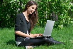 Mujer joven que se sienta en parque y que usa la computadora portátil Fotografía de archivo libre de regalías