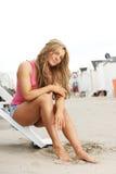 Mujer joven que se sienta en pasos en la playa con el barefeet en arena Foto de archivo