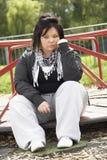 Mujer joven que se sienta en patio Fotos de archivo libres de regalías