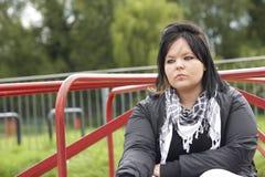 Mujer joven que se sienta en patio Imágenes de archivo libres de regalías