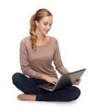 Mujer joven que se sienta en piso con el ordenador portátil Fotografía de archivo