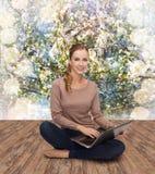Mujer joven que se sienta en piso con el ordenador portátil Fotos de archivo libres de regalías