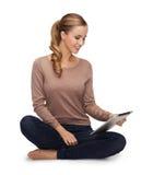 Mujer joven que se sienta en piso con PC de la tableta Fotografía de archivo libre de regalías