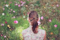 Mujer joven que se sienta en prado Fotografía de archivo