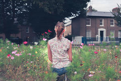Mujer joven que se sienta en prado Imagenes de archivo
