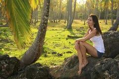 Mujer joven que se sienta en rocas en la arboleda de los árboles de coco, Las Galeras Fotografía de archivo