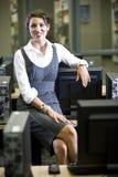 Mujer joven que se sienta en sala de ordenadores de la biblioteca fotografía de archivo
