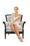 Mujer joven que se sienta en silla Fotografía de archivo libre de regalías
