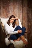 Mujer joven que se sienta en silla Fotografía de archivo