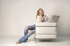 Mujer joven que se sienta en silla con una computadora portátil y un Cel Foto de archivo
