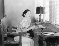 Mujer joven que se sienta en su escritorio que escribe una letra (todas las personas representadas no son vivas más largo y ningú imagen de archivo