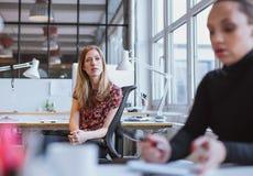 Mujer joven que se sienta en su escritorio que mira lejos de pensamiento Imagen de archivo libre de regalías