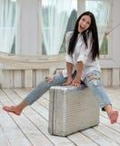 Mujer joven que se sienta en su maleta en casa Imágenes de archivo libres de regalías