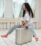 Mujer joven que se sienta en su maleta en casa Foto de archivo