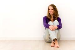 Mujer joven que se sienta en suelo Imágenes de archivo libres de regalías