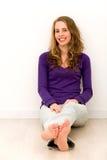 Mujer joven que se sienta en suelo Fotografía de archivo