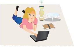 Mujer joven que se sienta en suelo con una computadora portátil Imagenes de archivo
