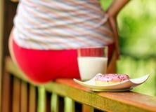 Mujer joven que se sienta en terraza con leche y el buñuelo Imagenes de archivo