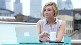 Mujer joven que se sienta en terraza del tejado usando el ordenador portátil almacen de metraje de vídeo