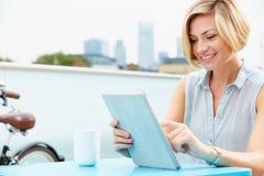Mujer joven que se sienta en terraza del tejado usando la tableta de Digitaces Imagen de archivo libre de regalías